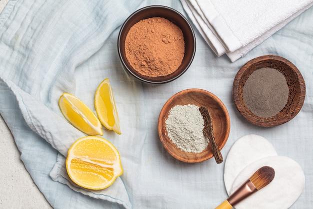 Différents types d'argile sèche dans des bols en bois pour la préparation de masques faciaux,
