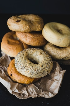 Différents types de bagels sur papier brun froissé sur fond noir