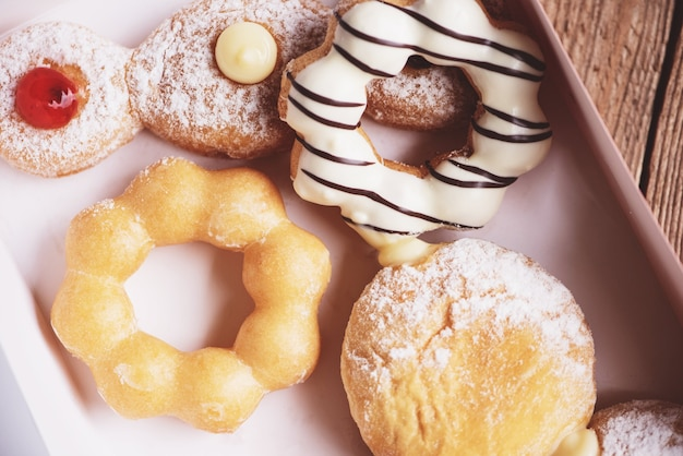 Différents types de beignets, beignets sucrés dans une boîte à beignets en papier dessert snack.