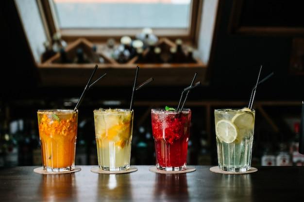 Différents types de boissons estivales dans des verres, des cubes de glace et une tranche de fruits sur une table sombre.