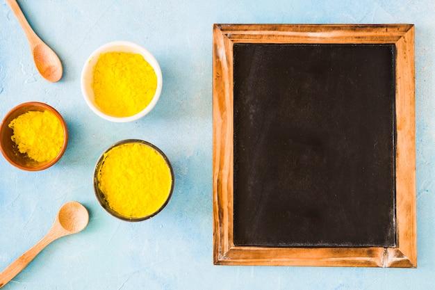 Différents types de bols avec de la poudre de couleur holi jaune et une cuillère près de l'ardoise vierge en bois