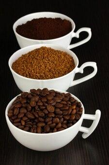 Différents types de café en trois tasses sur table en bois