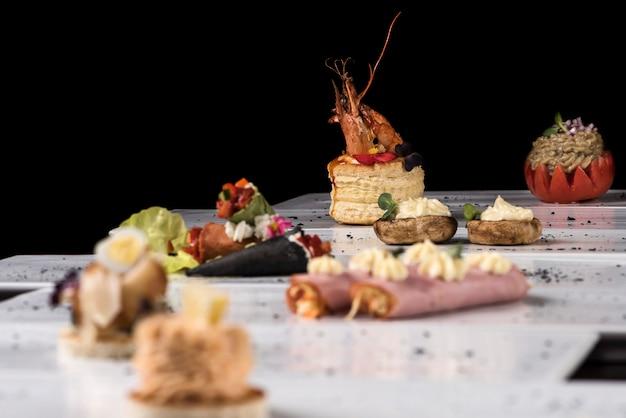 Différents types de canapés, placés sur des assiettes individuelles, bouchées, fond sombre