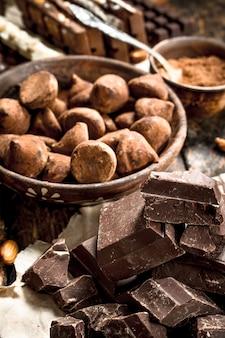Différents types de chocolat, de cacao en poudre et de morceaux de chocolat noir. sur un fond en bois.