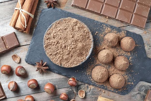 Différents types de chocolat, cacao en poudre, noisettes et autres épices. ingrédients pour faire des truffes maison.