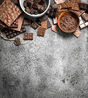 Différents types de chocolat dans des bols. sur une table rustique.