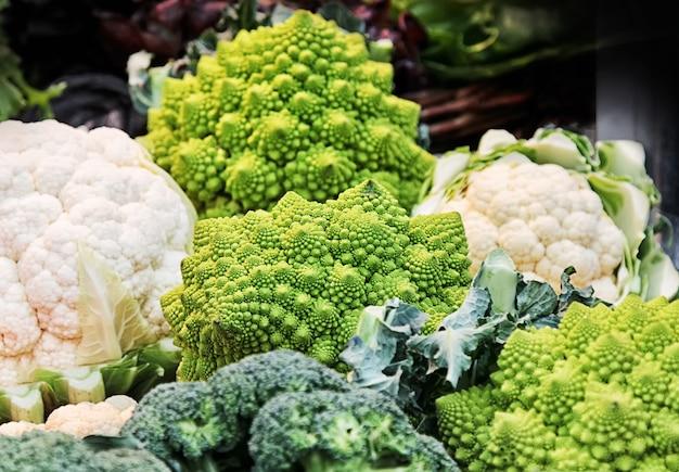 Différents types de chou (romanesco, brocoli, chou-fleur) dans un panier au marché.