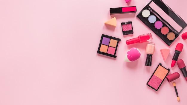 Différents types de cosmétiques dispersés sur une table rose
