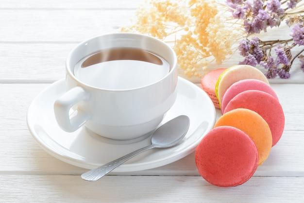 Différents types de couleur de macarons avec une tasse de thé chaud sur un fond en bois blanc