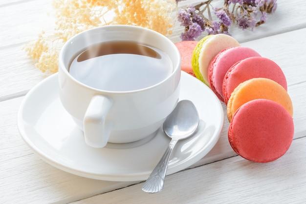 Différents types de couleurs de macarons avec une tasse de thé chaud sur du bois blanc