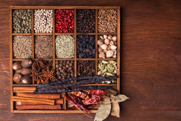 Différents types d'épices dans une boîte en bois sur la table