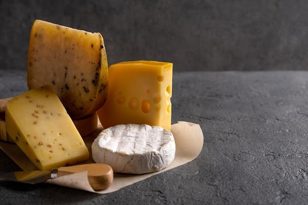 Différents types de fromage sur planche grise. sombre maussade. espace libre pour votre texte. fermer.