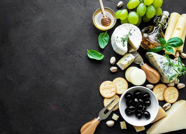 Différents types de fromage, raisins, miel et collations sur un fond de béton noir