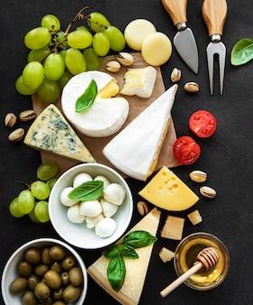 Différents types de fromage, raisins, miel et collations sur une surface en béton noir