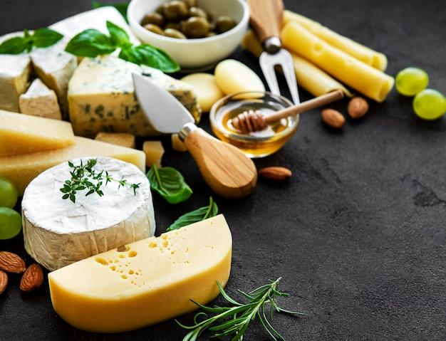 Différents types de fromage, raisins, miel et collations sur une table en béton noir