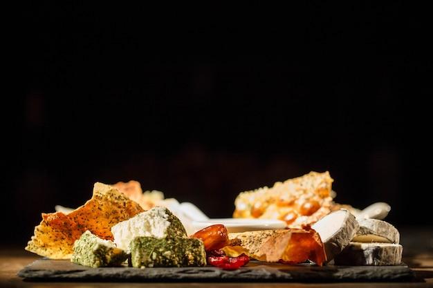 Différents types de fromage se trouvent sur une assiette noire