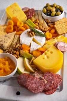 Différents types de fromages et charcuteries. vue de dessus sur fond blanc. fromages assortis avec noix, craquelins, olives, salami et romarin.