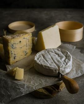 Différents types de fromages à pâte molle et dure sur planche de bois