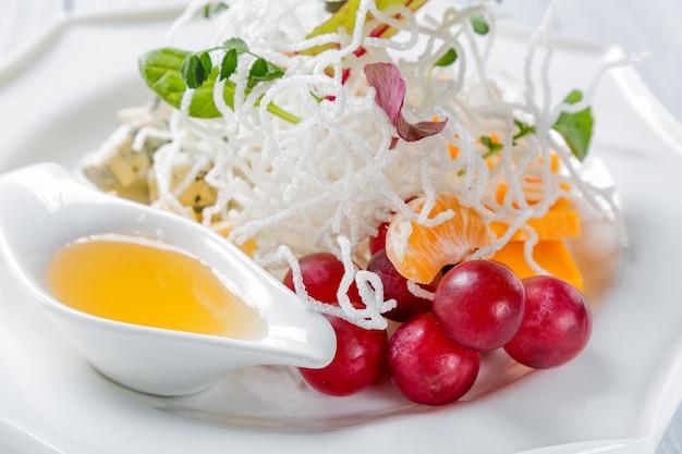 Différents types de fromages avec des raisins et de la noix sur une plaque blanche