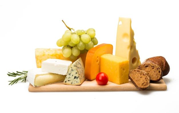 Différents types de fromages, tomates cerises, raisins et pain sur le plateau en bois