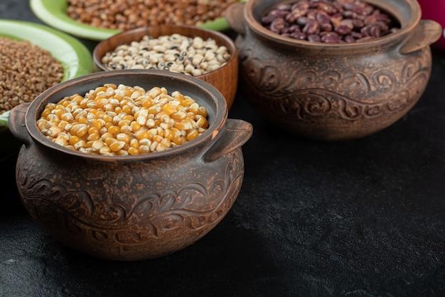 Différents types de graines de haricots, lentilles, pois dans des plats sur fond noir.