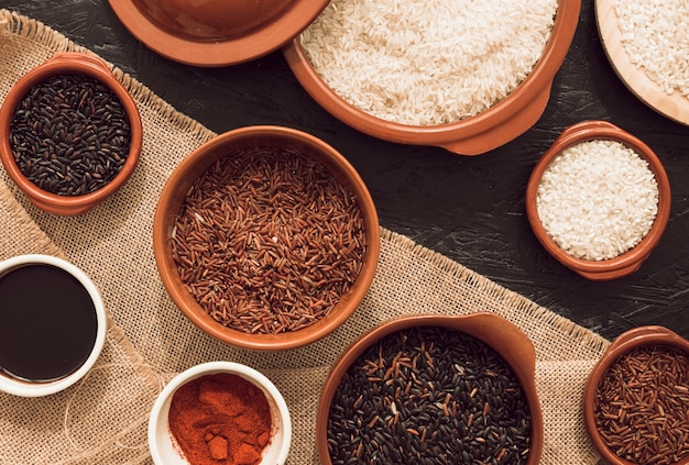 Différents types de grains de riz biologiques sur le sac et fond de texture rugueuse