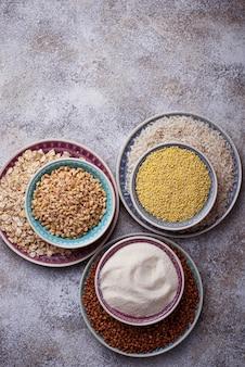 Différents types de gruaux: riz, semoule, blé, flocons d'avoine, avoine, sarrasin. vue de dessus