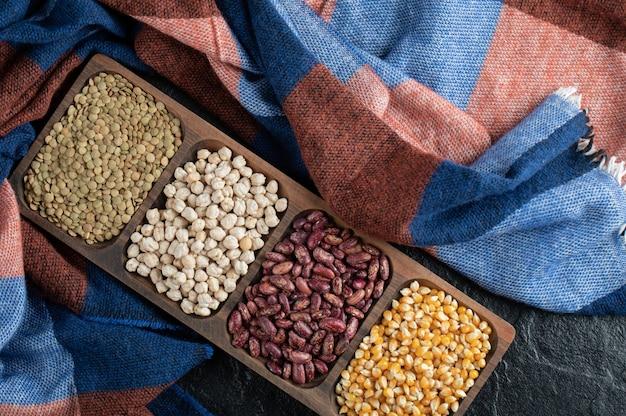 Différents types de haricots sur des assiettes en bois.