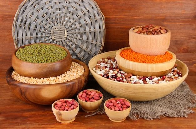 Différents types de haricots dans des bols sur fond de bois