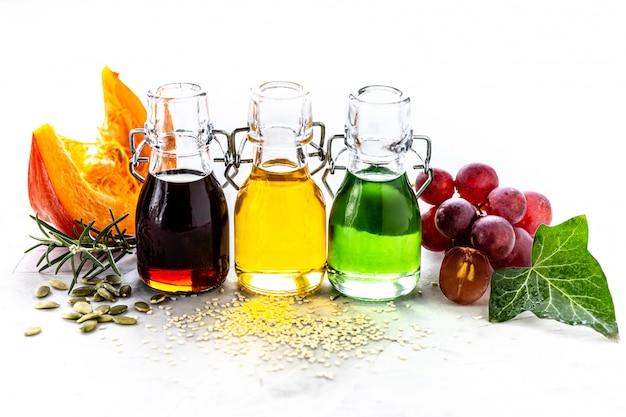 Différents types d'huile végétale en bouteilles de verre: sésame, lin, huile de raisin.