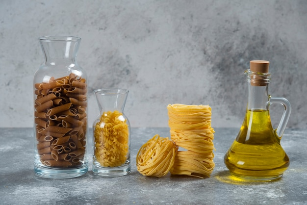 Différents types de macaronis crus avec une bouteille en verre d'huile.