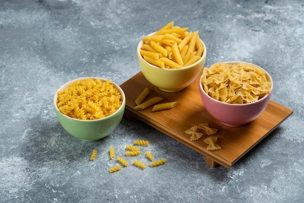 Différents types de macaronis crus sur planche de bois.