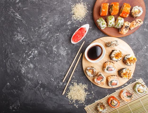Différents types de makis sushi au saumon sur un fond de béton noir