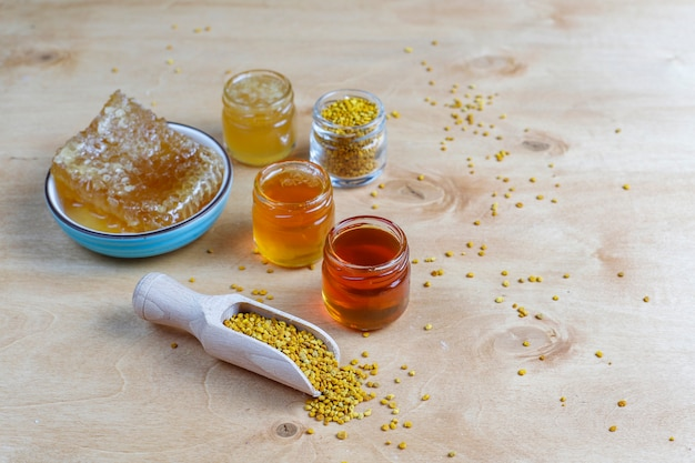 Différents types de miel dans des bocaux en verre, nid d'abeille et pollen.
