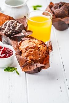 Différents types de muffins sur une table blanche avec jus et lait au petit déjeuner.