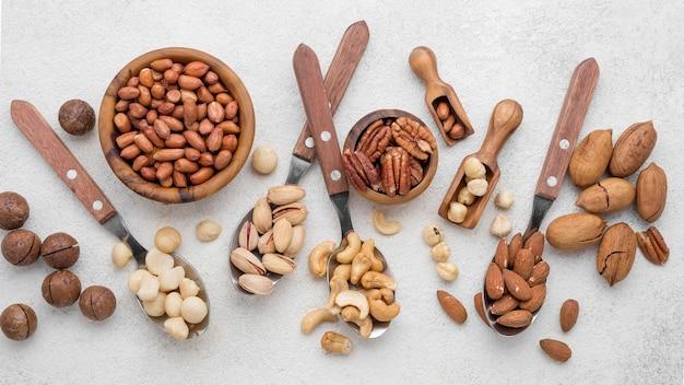 Différents types de noix avec des cuillères et des bols