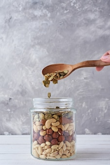 Différents types de noix et de graines dans un bocal en verre, gros plan