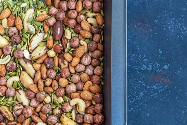 Différents types de noix sur une plaque à pâtisserie. noix de cajou rôties, noisettes, amandes et noix du brésil