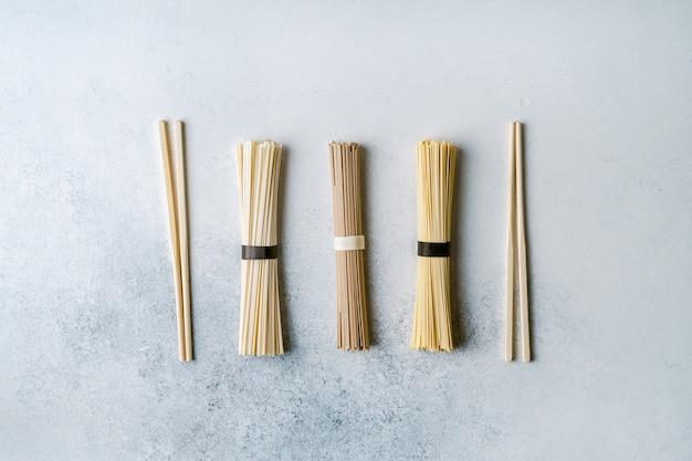 Différents types de nouilles et baguettes asiatiques longues et sèches