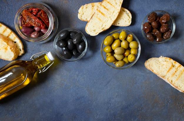 Différents types d'olives, bruschetta, tomates séchées et huile d'olive. snacks méditerranéens. vue de dessus.