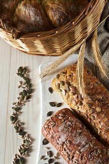 Différents types de pain aux graines sur un fond en bois blanc.