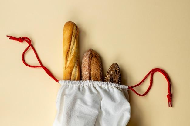 Différents types de pain la baguette française, le pain de seigle à grains entiers et le pain sans levure sont emballés dans un sac en coton réutilisable. le pain est partout sur la tête.