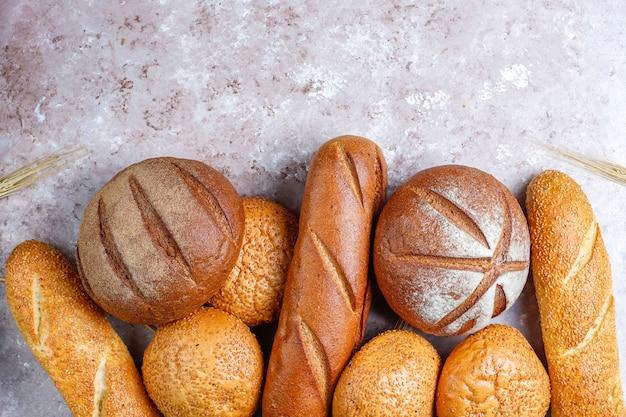 Différents types de pain frais en arrière-plan, vue de dessus