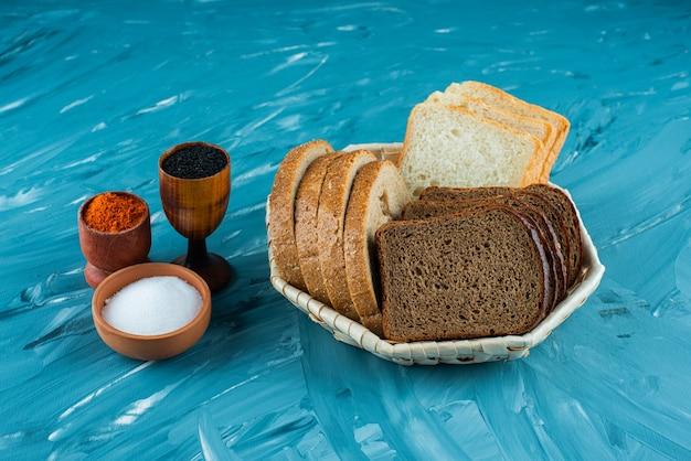 Différents types de pain frais dans un panier avec du sel et du poivre sur un fond clair.