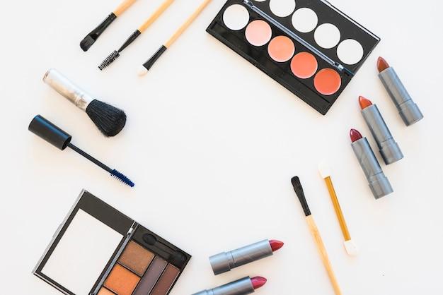 Différents types de palette de maquillage coloré; rouge à lèvres; mascara; pinceau sur fond blanc