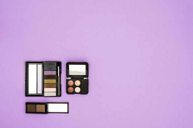 Différents types de palette d'ombres à paupières sur fond violet