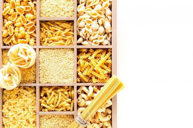 Différents types de pâtes alimentaires non cuites dans une boîte en bois, pâtes de blé entier, pâtes, spaghetti, nouilles, tagliatelles. espace copie