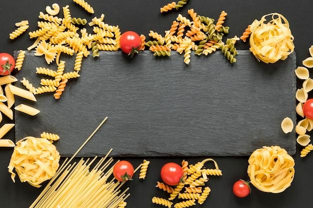 Différents types de pâtes alimentaires non cuites réparties autour de la pierre d'ardoise noire