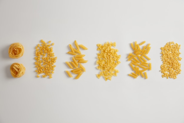 Différents types de pâtes crues crues sur fond blanc. les nids de pâtes, farfalle, tripolini, penne, fusilli peuvent être utilisés pour les sauces ou les plats. variété de produits italiens. formes variées. concept alimentaire