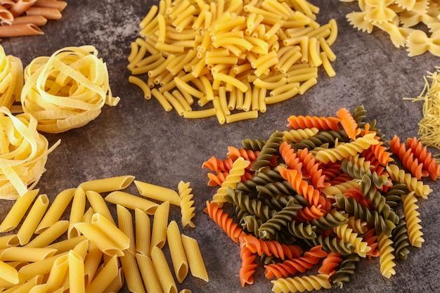 Différents types de pâtes crues isolés sur la surface grise